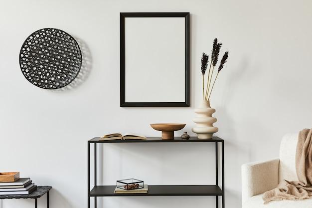 Composizione elegante e minimalista del design d'interni di una stanza creativa con cornice per poster finto, ripiano in metallo, poltrona e accessori personali. concetto in bianco e nero. modello.