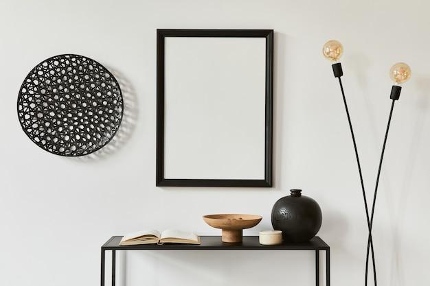 Composizione elegante e minimalista del design d'interni di una stanza creativa con cornice per poster finta, mensola in metallo, lampada industriale e accessori personali. concetto in bianco e nero. modello.
