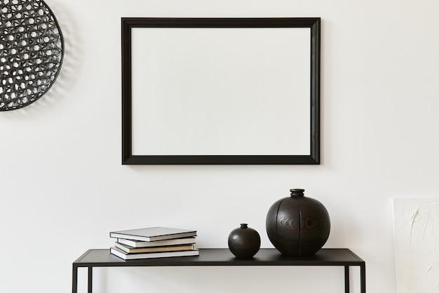 Composizione elegante e minimalista del design d'interni di una stanza creativa con cornice per poster finto, ripiano in metallo e accessori personali. concetto in bianco e nero. modello.