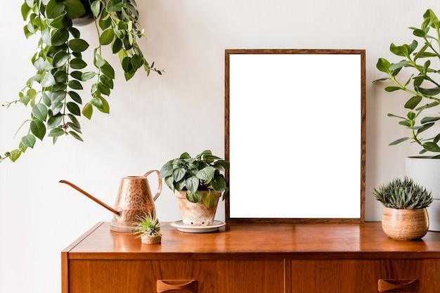 Concetto di cornice per poster minimalista ed elegante con mobili retrò, pianta sospesa, lampada da tavolo, decorazioni e accessori eleganti. muri bianchi.