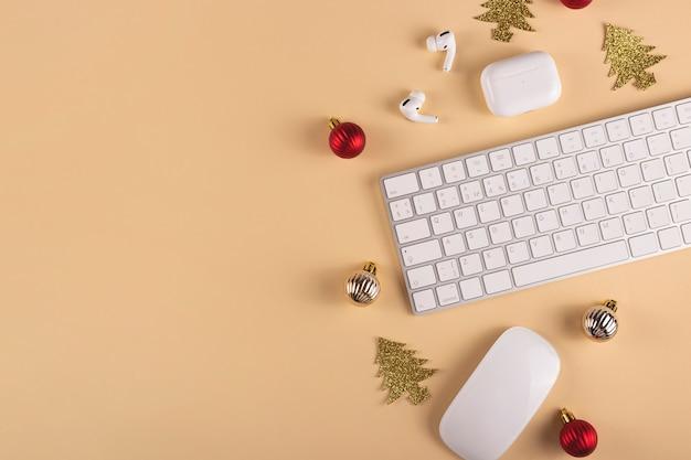 Ambiente di lavoro elegante minimalista tra decorazioni natalizie su uno sfondo neutro vista dall'alto e spazio di copia
