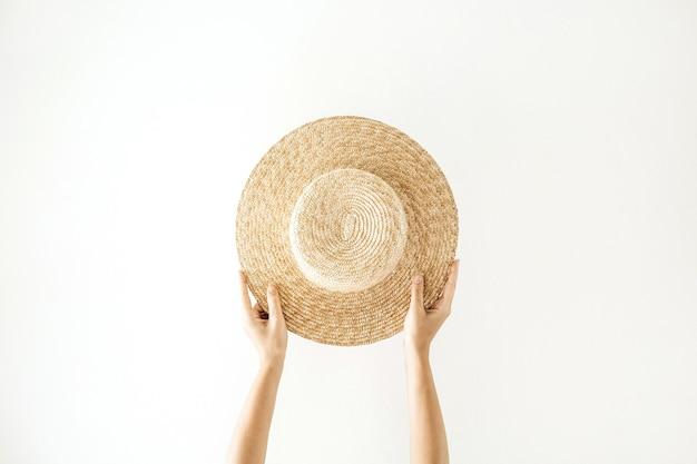 Estate minimalista e concetto di viaggio. mani della donna che tengono un cappello giallo paglierino