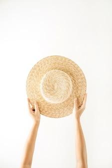 Estate minimalista e concetto di viaggio. mani di donna che tengono un cappello giallo paglierino. sfondo minimo isolato