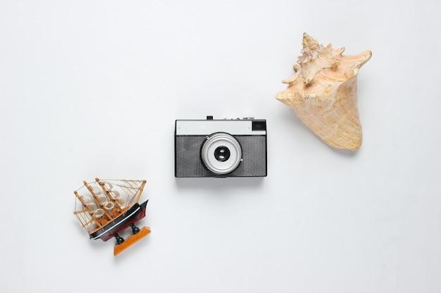 Viaggio minimalista ancora in vita. seashells, fotocamera retrò, nave decorativa su sfondo bianco. vista dall'alto