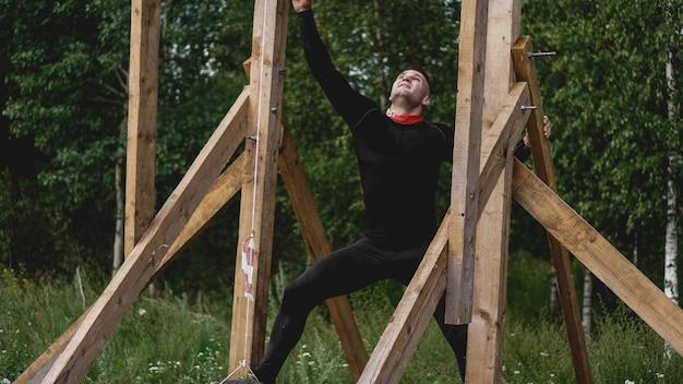 Minsk bular. 28 luglio 2019 giornata di sole. uomo che passa attraverso gli ostacoli durante la corsa ad ostacoli nello stivale o nella competizione sportiva