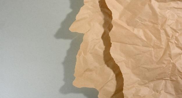 Pezzo di carta marrone menta con bordi strappati e ombra su sfondo grigio. sfondo creativo astratto per designer, copia spazio