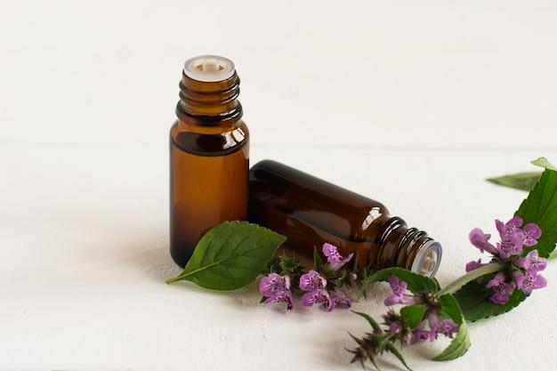 Olio essenziale di menta con estratto di foglie su fondo bianco con fiori di piante. il concetto di piante aromatiche medicinali naturali.