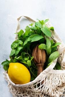 Foglie di menta, limone fresco e miele che si trovano tenendo la borsa di cotone per la spesa in rete sul vecchio cemento grigio.