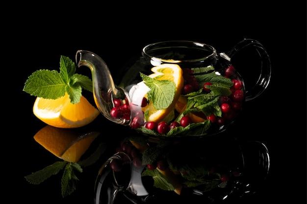 Tè alla menta con arancia e mirtilli rossi su sfondo nero