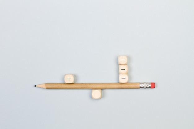 Segni più e meno cubi di legno con una matita in equilibrio