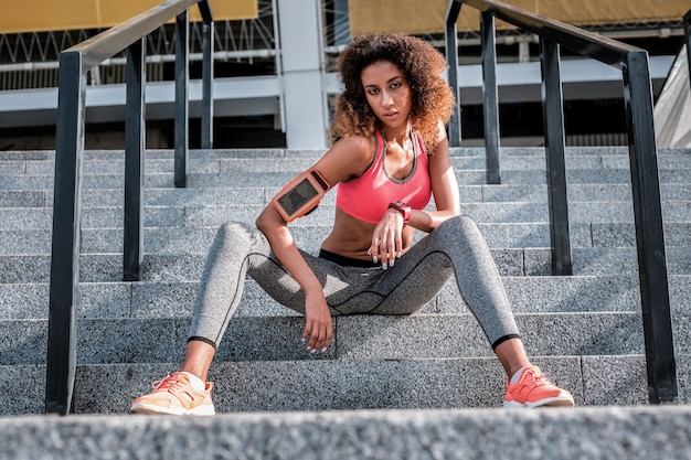 Minuto per riposare. attraente donna abete seduta sulle scale pur avendo un periodo di riposo dall'allenamento