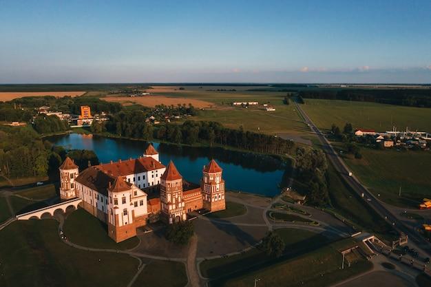 Castello di mir con guglie vicino alla vista dall'alto del lago in bielorussia vicino alla città di mir.