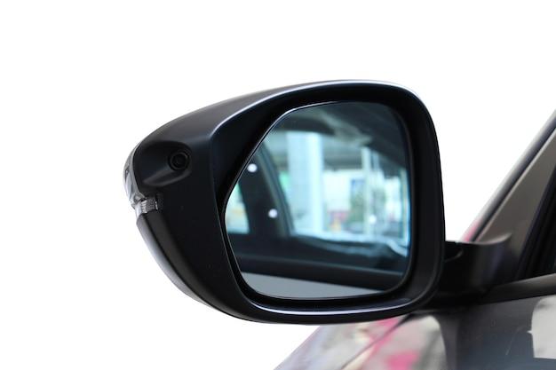 Specchio di auto con fotocamera digitale su sfondo bianco.
