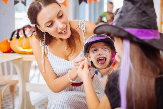 Specchio e trucco. bella madre alla moda amorevole che tiene miracolo che mostra alla figlia il suo trucco di halloween