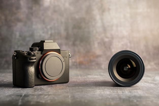 Fotocamera digitale mirrorless e obiettivo su grigio