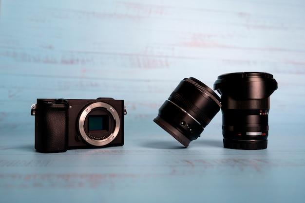 Fotocamera digitale mirrorless con obiettivi su blu.