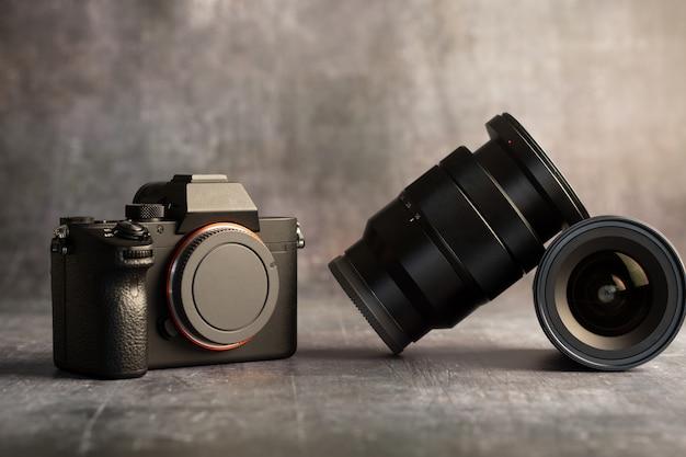 Fotocamera digitale mirrorless con obiettivi su grigio. concetto di tecnologia