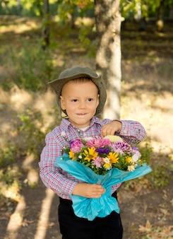 Ragazzino malizioso con un cappello in stile cowboy che tiene un grande mazzo di fiori incartati in regalo in piedi nel bosco