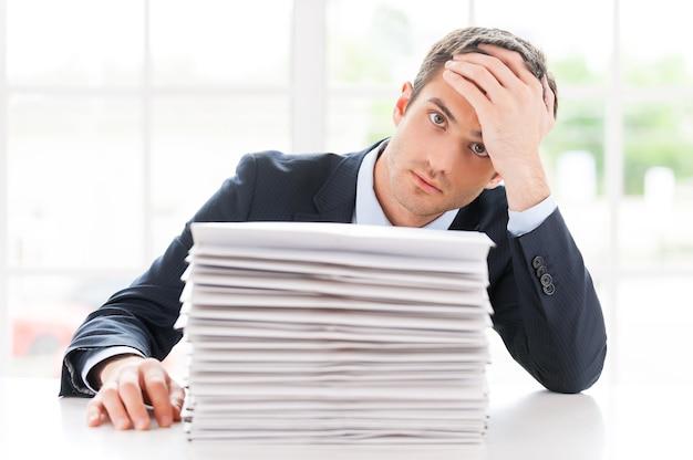 Scadenze mancanti. giovane depresso in camicia e cravatta che guarda l'obbiettivo e tiene la testa in mano mentre è seduto al tavolo con una pila di documenti su di esso