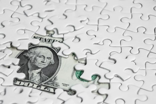Pezzi di puzzle mancanti su sfondo dollaro denaro, concetto di soluzione aziendale, chiave per il successo