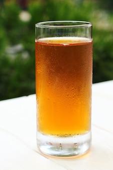 Bicchiere appannato con succo sulla terrazza estiva. fotografia ravvicinata, ripresa macro.
