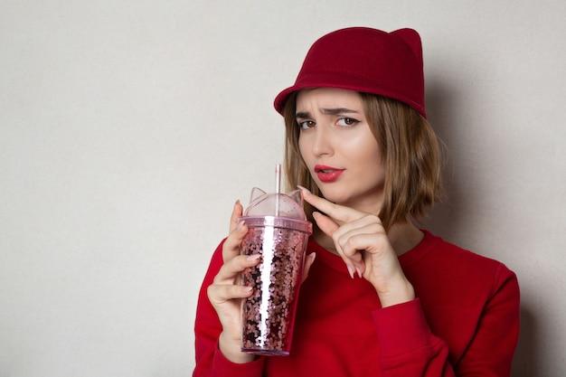 Diffidente ragazza bruna che indossa berretto rosso e maglione, tenendo cocktail in studio. spazio per il testo