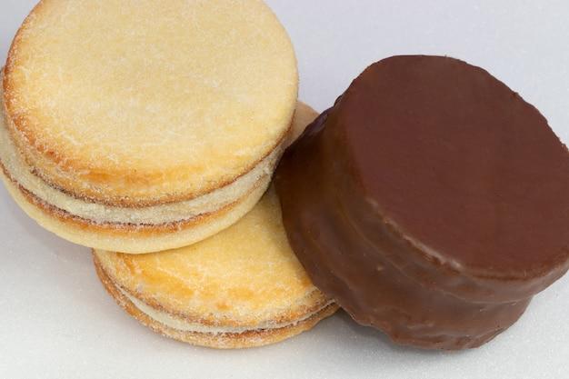 Mix di alfajores ricoperti di cioccolato e farciti con dulce de leche su sfondo bianco.