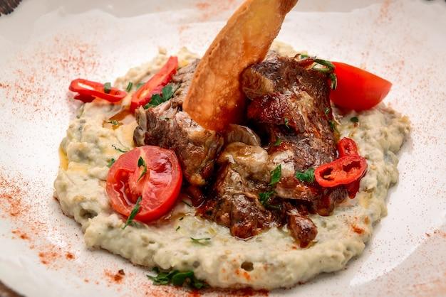 Mescolare il porridge di orzo e grano con carne di tacchino al forno in una ciotola sulla tavola di legno bianca, vista dall'alto. concetto di cibo sano