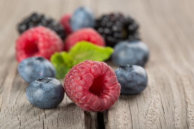Misto di frutti di bosco. lamponi, mirtilli e more sul vecchio un primo piano di tavolo in legno