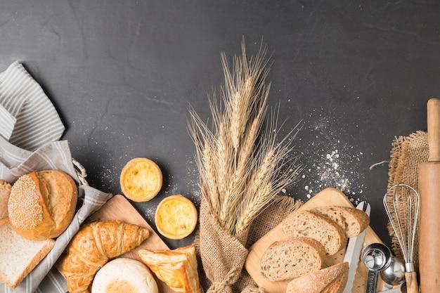 Mescolare pane, croissant, baguette, muffin e torta all'uovo su sfondo di pietra nera, vista dall'alto e spa copia