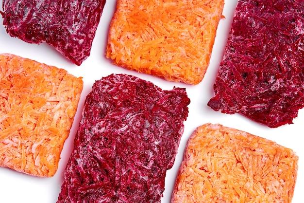 Mescolare mattoni di barbabietole e carote grattugiate congelate. approvvigionamento di alimenti surgelati. semilavorato.