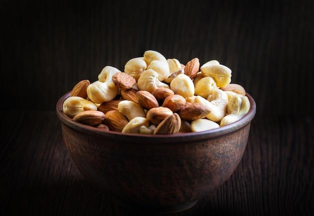Mix di anacardi e mandorle in un piatto di argilla su uno sfondo di legno scuro