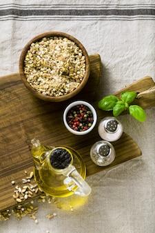 Mix di cereali in una ciotola di legno su un tagliere con olio d'oliva, peperoni multicolori e spezie. cucina casalinga sulla tovaglia di lino