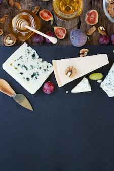 Mix di formaggio sul tagliere nero con miele e fichi, vista dall'alto, copia spazio su pietra nera