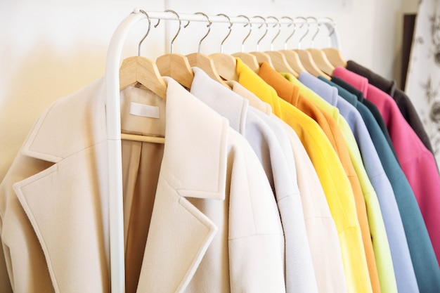 Mescoli la fila colorata di cappotto femminile sul gancio.