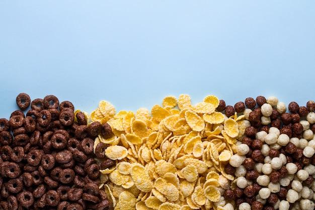 Mix di palline secche, di cioccolato, anelli e corn flakes gialli per cereali colazione su sfondo blu