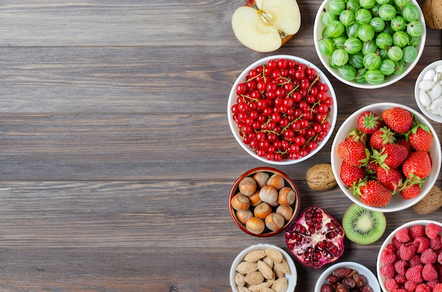 Mix di bacche fresche, noci e frutta. il cibo sano contiene molte vitamine e utili oligoelementi. fondo in legno marrone. copia spazio.