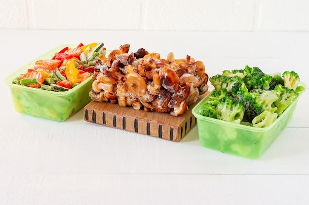 Mix di verdure e funghi surgelati in contenitori di plastica. scorte di farina per l'inverno.