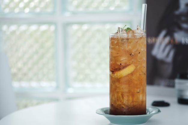 Mescolare la bevanda di ghiaccio tè alle erbe ghiacciato, tè al limone in un bicchiere alto su sfondo sfocato, spazio di copia.