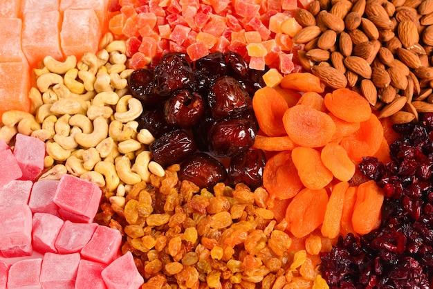 Mix di noci e frutta secca e dolci delizie turche sullo sfondo.