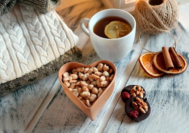 Mescolare frutta secca e cioccolato con una tazza da tè e un maglione al concetto invernale della tavola bianca