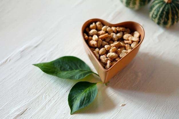 Mescolare le foglie verdi del piatto a forma di cuore di noci su uno sfondo bianco nutrizione sana