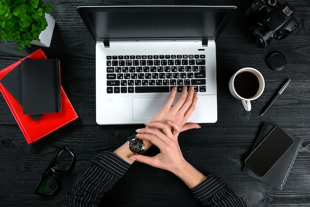 Mix di forniture per ufficio e gadget su uno sfondo di scrivania in legno vista dall'alto