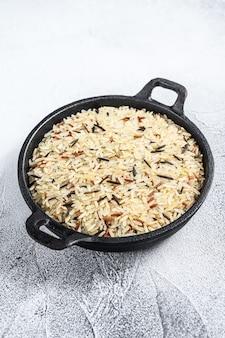 Mescolare il riso in una padella di ghisa. sfondo bianco. vista dall'alto.