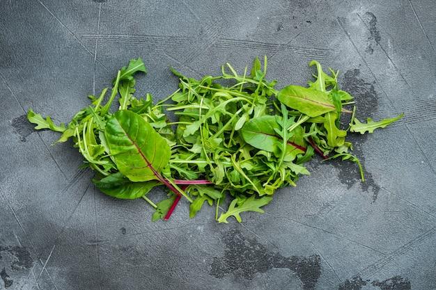 Mescolare foglie di insalata, bietole e set di rucola, su pietra grigia sullo sfondo, vista dall'alto laici piatta