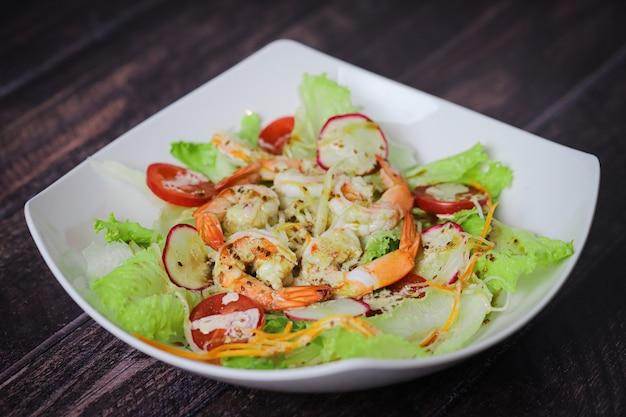 Mix di insalata con gamberetti nel piatto bianco sul tavolo in legno, ravanello e pomodorini, cibo sano.
