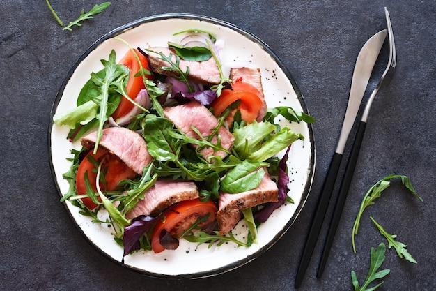 Mescolare insalata con pomodori e manzo medio in un piatto su uno sfondo scuro.