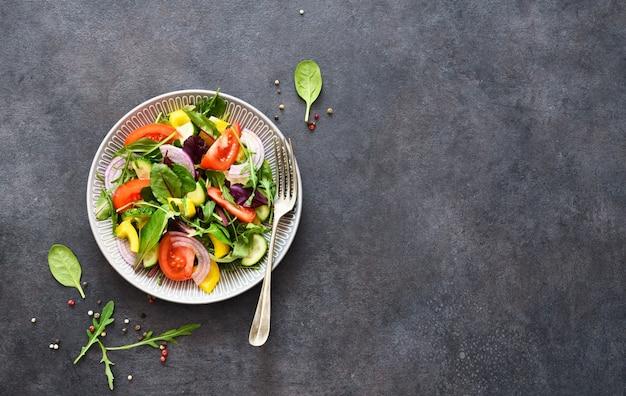 Mescolare insalata con pomodori, cipolle e olio d'oliva in un piatto su uno sfondo di cemento nero.
