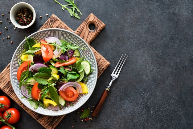Mescolare insalata con pomodori, cipolle e olio d'oliva in un piatto su una tavola di legno su uno sfondo di cemento nero.