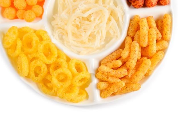 Mix di snack su un piatto bianco isolato su bianco.